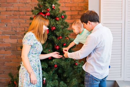 family  room: Happy family decorating Christmas tree in the room.