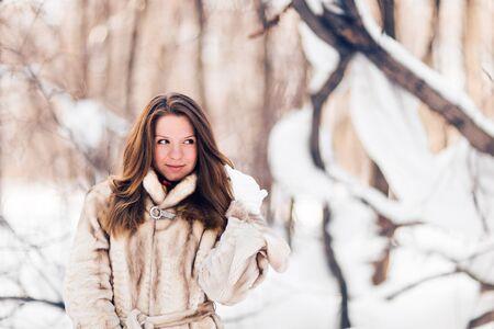 Winter portrait of young beautiful woman wearing fur coat. Snow winter beauty fashion concept