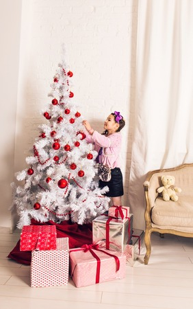 8 years old: 8 years old little girl decorating Christmas tree at home