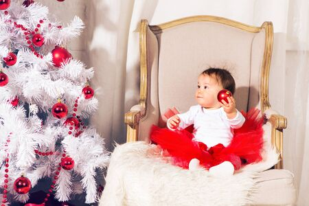 happy baby child girl near a Christmas tree. Stock Photo