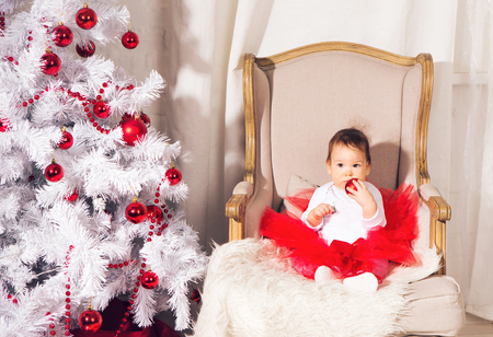 Baby with christmas background. happy baby child girl near a Christmas tree. Stock Photo