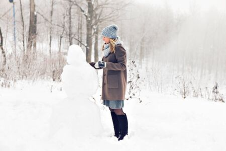 mornings: Woman making a snowman in winter time.