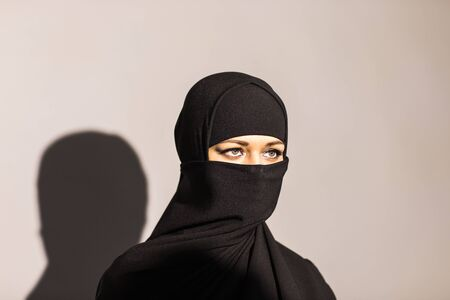 niqab: Young woman wearing black niqab on background.
