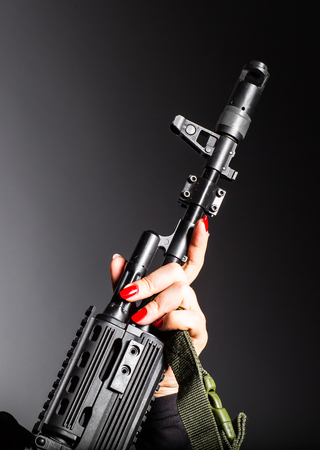 Close up of womans hand holding army weapon machine gun
