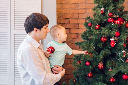 Father and son are decorating the Christmas tree. Stock Photo