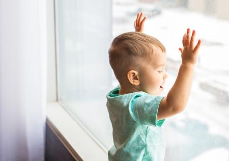 adentro y afuera: Niño mirando por la ventana. Bebé, niño