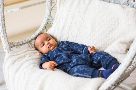 biracial: Thoughtful biracial mix of Hispanic and African American infant lying down on yellowish colored blanket Stock Photo