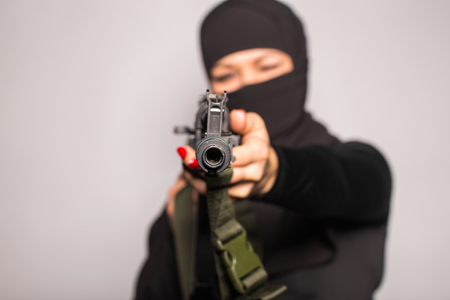 tommy: Muslim woman with machine gun. Armed female warriors of Islam. Terrorist woman in Muslim clothes holding a submachine gun. Woman in black with gun Stock Photo