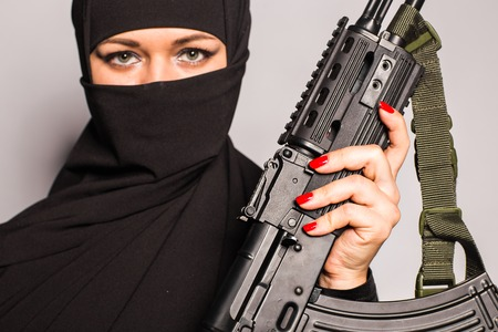 Muslim woman with machine gun. Armed female warriors of Islam. Terrorist woman in Muslim clothes holding a submachine gun. Woman in black with gun Reklamní fotografie