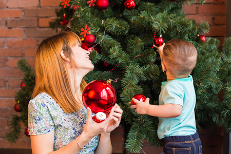 mother and baby deer: Little boy helping his mom to decorate christmas tree Stock Photo