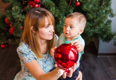 Little boy helping his mom to decorate christmas tree Stock Photo