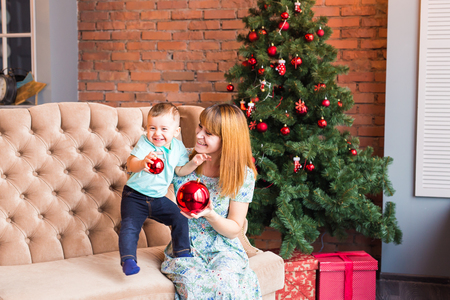 Smiling mother playing with lovely baby son near Christmas tree.