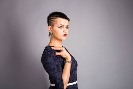 short haircut: Portrait of young beautiful woman with stylish short haircut over grey background.
