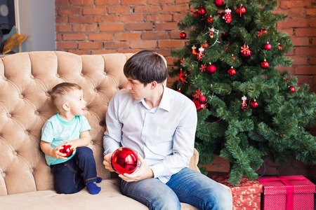 Happy young father playing with his baby son near Christmas tree. Stock Photo