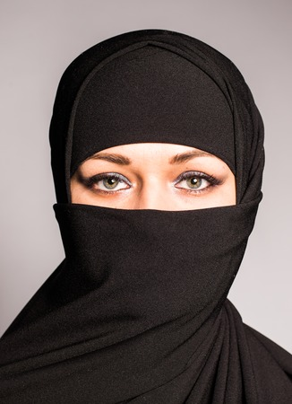 niqab: Portrait of an arabic young woman with her beautiful blue eyes in traditional islamic cloth niqab Stock Photo