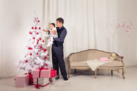 family, children, christmas, x-mas, love concept - happy father with adorable baby daughter near christmas tree.