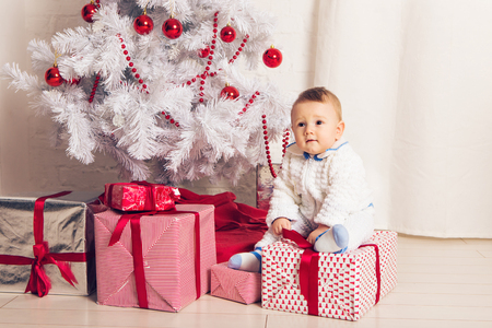 Cheerful little baby boy playing near the Christmas tree.