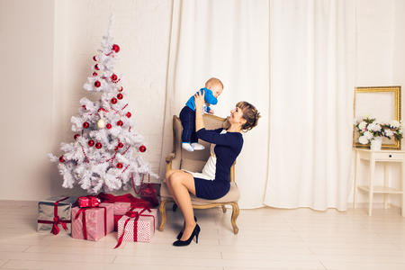 festively: happy family mother and baby little son playing home on Christmas holidays. New Years holidays. Toddler with mom in the festively decorated room with Christmas tree. Portrait of mother and baby boy. Stock Photo