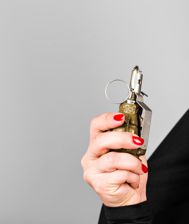 Hand grenade in a young womans hand. Stock Photo
