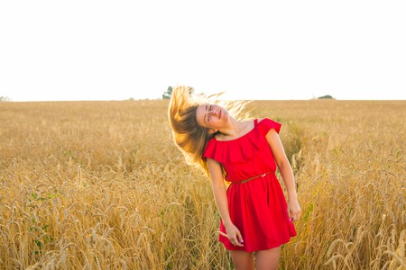 dress blowing in the wind: Gorgeous Romantic Girl Outdoors. Beautiful Model in Short Dress in Field. Long Hair Blowing in the Wind. Backlit, Warm Color Tones Stock Photo