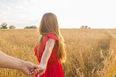 Follow me, Beautiful young woman holds the hand of man in a wheat field.
