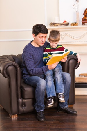 tailes: Portrait of happy parent and his son reading fairy tailes.