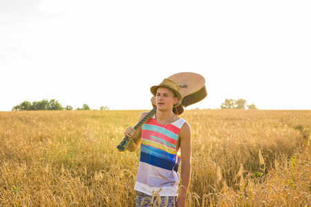traveler, romantic concept - guy with guitar walking in field