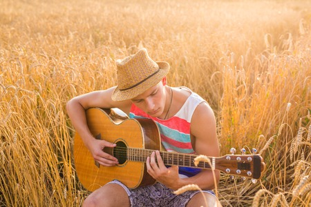 Happy handsome man is playing guitar in the field Stock Photo