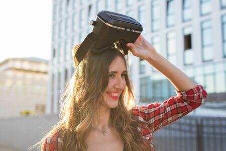 Beautiful young woman wearing virtual reality headset in an urban context