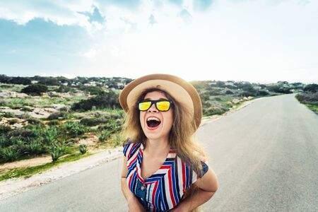 Closeup of delighted happy young pretty woman in sunglasses on summer day outdoors background