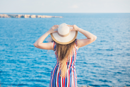 Back view of woman standing in summer dress and hat looking out towards blue ocean and sky Stock Photo
