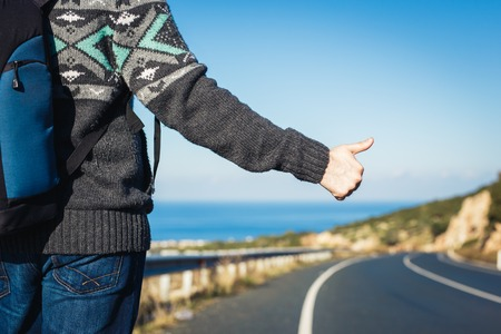 road trip, travel, gesture and people concept - hitchhiker stopping car with thumbs up hand sign Standard-Bild