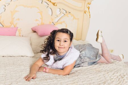 Cute asian child girl lying on white bed