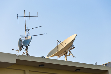 satelite: satellite dish and TV antennas on the house roof with blue sky background