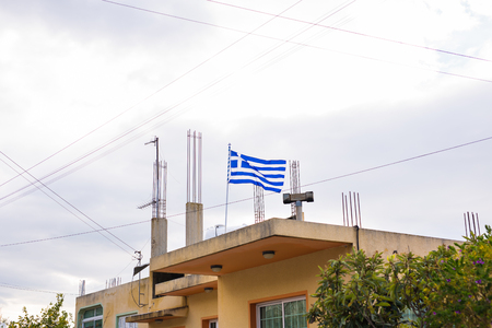 european economic community: Greek flag on the roof of building, waving in the wind