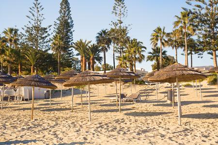 unoccupied: Straw umbrellas on empty seaside beach in Greece