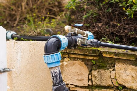 Concept of water supply, water, irrigation systems - Plastic pipe outdoors. Stock Photo