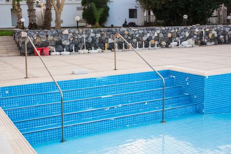 gunk: Empty swimming pool with metal ladder.