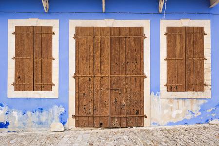scraped: Old wooden door with metal hinges and lock
