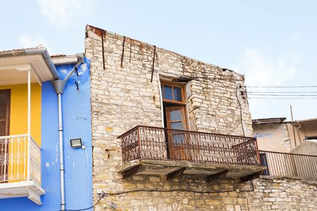 old items: The balcony on the ruined building. Detail of a wall of an old almost ruined house with balconies.