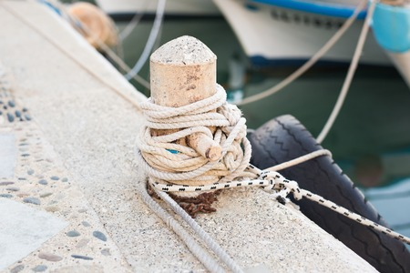 tiedup: Wooden post with mooring ropes for tying boats and ships