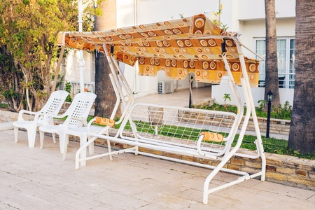 round chairs: White outdoor furniture. Lounge chairs in hotel garden invite you to relax