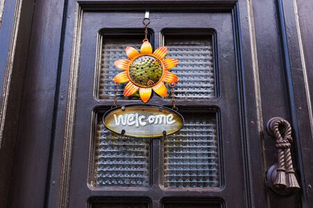 come home: Welcome sign with flower on the door