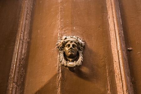 Traditional ornate door handle or knocker against a wooden door Stock Photo