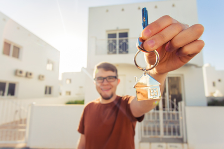 joyfully: Concept of housewarming, real estate, new home - Young man holding key of new house. Stock Photo
