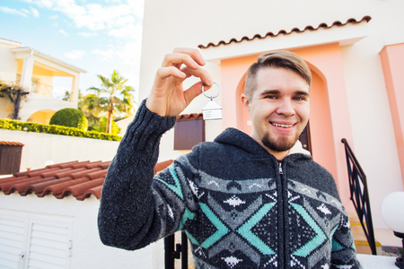 first time buyer: Concept of housewarming, real estate, new home - Young man holding key of new house. Stock Photo