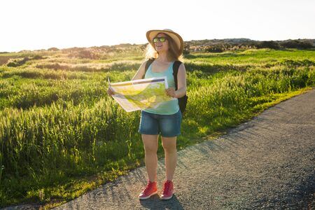 Tourism, travel and summer concept - Happy woman traveler with backpack checks map to find directions.