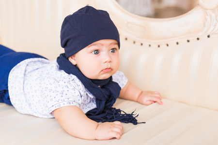 close up portrait of cute baby boy wearing blue hat stock photo