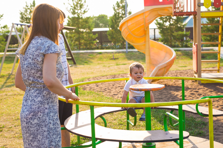 summer, childhood, leisure and family concept - happy child and his parents on children playground climbing frame
