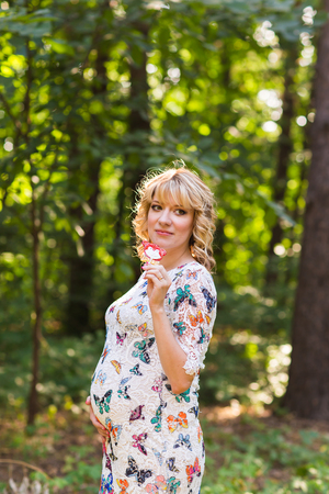 pacification: Outdoor portrait of young pregnant woman holding a lollipop in summer nature Stock Photo
